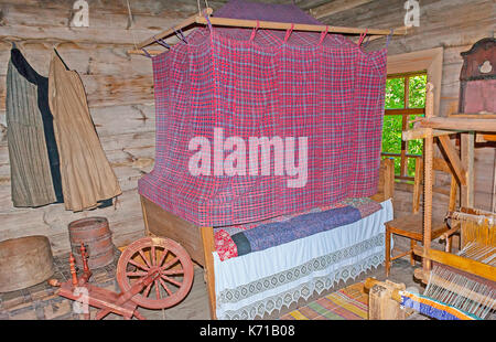 SUZDAL, RUSSIA - JULY 1, 2013: Recreated interior of living chamber in log peasant house with a bed and canopy, - Stock Photo