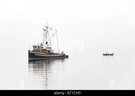 Fishing boat near Port Townsend during Wooden Boat Show in fog with row boat. - Stock Photo