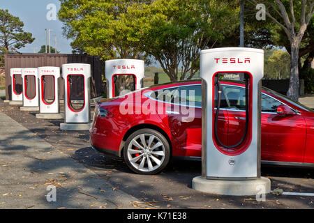 Tesla 'S'  sedan connected to 480 volt  Supercharger (fast charging)  Station. - Stock Photo