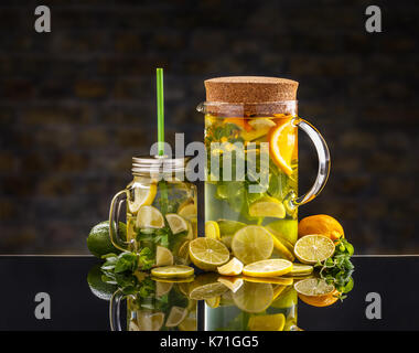 Cold lemon water with fresh fruits in a jar and in a jug - Stock Photo