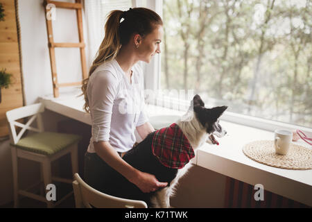 Beautiful woman happy while spending time with her dog at home - Stock Photo