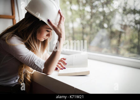 Beautiful woman studying for hard university exam by reading boo - Stock Photo