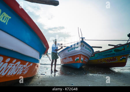 Two Fishermen  manage their nets on the beach on Tranquebar in Tamil Nadu in Southern India - Stock Photo