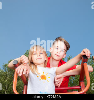 Low angle view of brother and sister posing on a climbing frame in a summer playground looking at camera - Stock Photo
