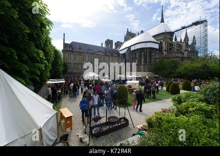France, Marne, Reims, People walking along stalls of various products in gardens of Tau Palace with the cathedral - Stock Photo