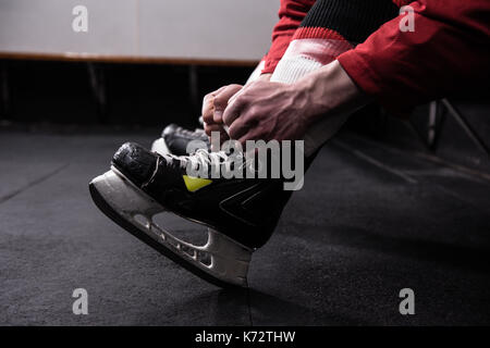 Low section of male hockey player tying ice skate in dressing room - Stock Photo
