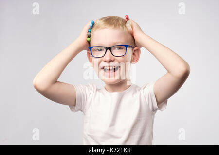 Happy little boy laughs holding markers in hands. - Stock Photo