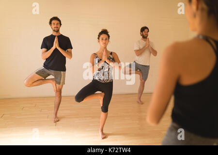 Yoga instructor guiding student in doing tree pose at yoga studio - Stock Photo