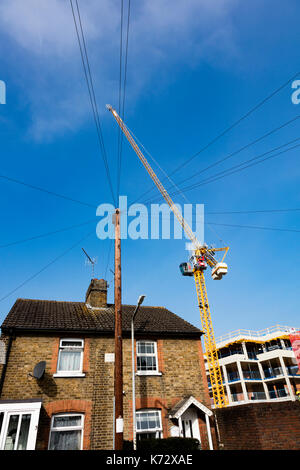 A huge crane towers over cottages on Holford Street, Tonbridge, Kent,, as it lifts building materials on a development - Stock Photo