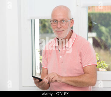 a mature man with eyeglasses typing message on smartphone - Stock Photo