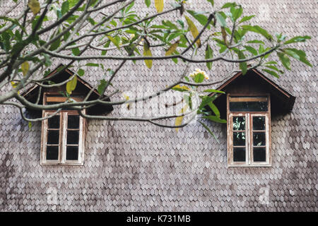 Small wooden windows on tile roof. Old european style house - Stock Photo