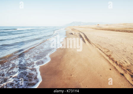 Fantastic views of the sea coast with yellow sand and blue water - Stock Photo