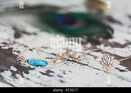 Golden jewelry bracelet with blue gemstone on wooden shabby background