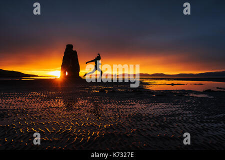 Is a spectacular rock in the sea on the Northern coast of Iceland. On this photo Hvitserkur reflects in the sea - Stock Photo