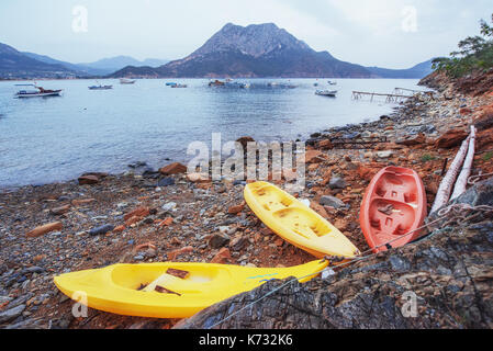 Three boats on the beach and boats in the sea in the background - Stock Photo