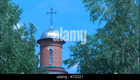 Orthodox temple orange brick with sunny ray, flowering green trees in foreground. Blue sky white clouds. Pray, holy - Stock Photo
