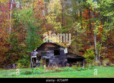 A view of  an old wooden barn surrounded by colorful trees in the middle of fall in Georgia, USA - Stock Photo