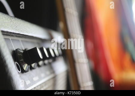 A musicians bass guitar and a bass amp with a tie dye tapestry in the background. - Stock Photo