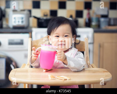 Asian baby girl eating toasted at home kitchen - Stock Photo