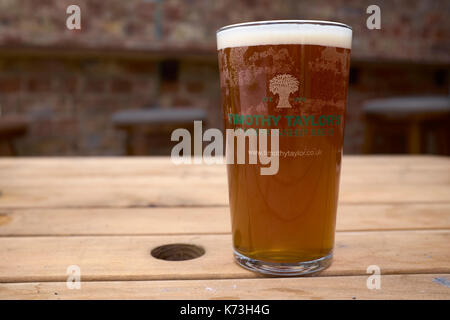 Pint of Timothy Taylor's bitter on a wooden table, Yorkshire, United Kingdom - Stock Photo