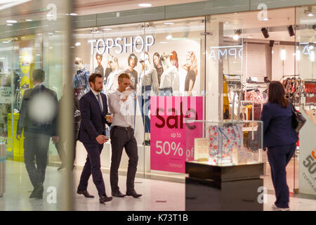 London, UK - September 15, 2017 - Topshop display window in Canary Wharf with a on sale sign while office workers - Stock Photo