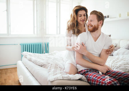 Beautiful happy couple waking up smiling in bedroom - Stock Photo