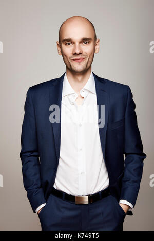 Studio shot of young man in suit. Gray background. - Stock Photo