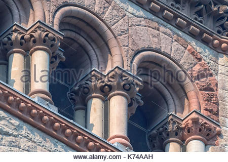Old City Hall Richardsonian Romanesque Revival architectural details.Columns and arches in windows.  The red stone - Stock Photo