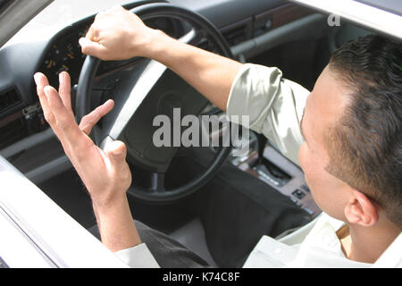 Man frustrated sitting in traffic - Stock Photo