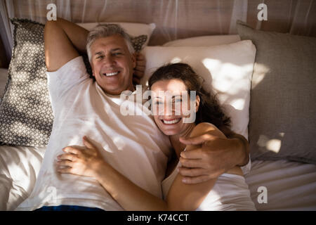 Portrait of happy couple relaxing in canopy bed during morning - Stock Photo