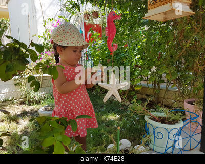 little cute girl plays with garden toys in curiosity - Stock Photo
