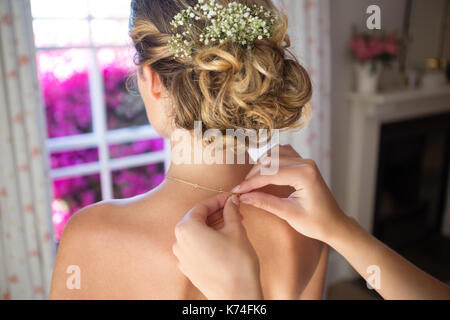 Cropped hands of bridesmaid fastening bride chain in dressing room - Stock Photo