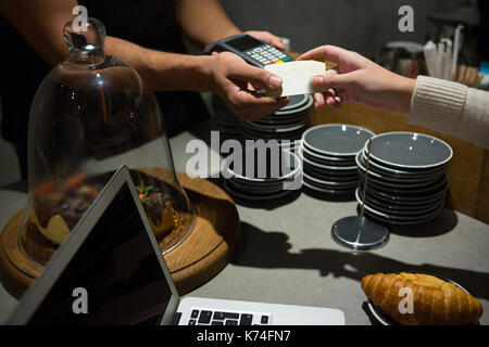 Customer making payment through credit card at counter in restaurant - Stock Photo