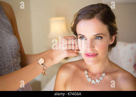 Midsection of bridesmaid dressing bride in fitting room - Stock Photo