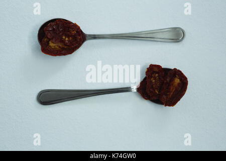 Dried red chili peppers in spoon on white background - Stock Photo