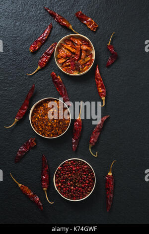 Overhead of dried red chili pepper and crushed red pepper in bowl - Stock Photo