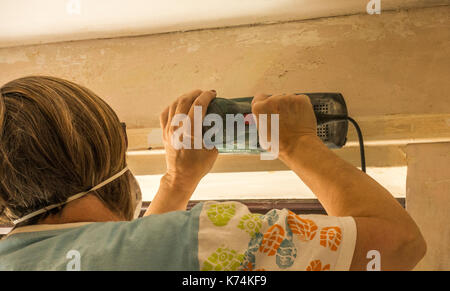 A woman wearing a dust mask on her face, while sanding wood with a power tool, in a room in her home she is decorating - Stock Photo
