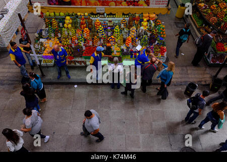 The life in the Mercado Municipal in Sao Paulo, Brazil with vendors and costumers around a fruit and vegetable stand, - Stock Photo