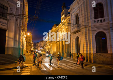 Bolivians walking in colonial street at night in the city Sucre, constitutional capital of Bolivia in the Oropeza - Stock Photo