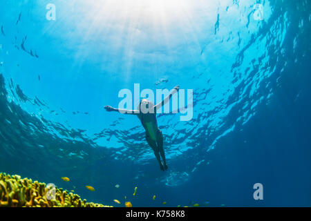 Happy family - girl dive underwater with tropical fishes in coral reef sea pool. Travel lifestyle, water sport outdoor - Stock Photo