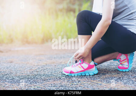 Young female workout before fitness training session at the park. Healthy young woman warming up outdoors. - Stock Photo