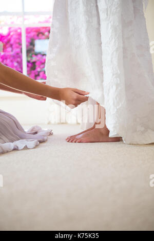 Cropped hands of bridesmaid adjusting bride dress in fitting room - Stock Photo