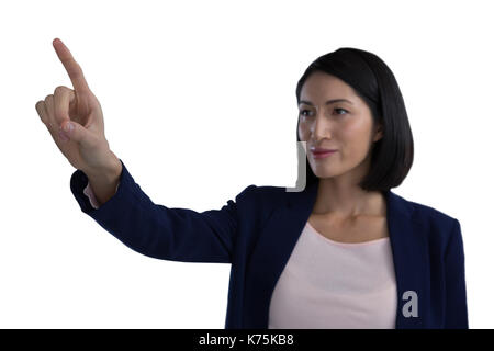 Businesswoman touching invisible screen against white background - Stock Photo