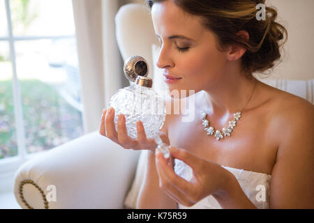 Beautiful bride smelling perfume while sitting on armchair at home - Stock Photo