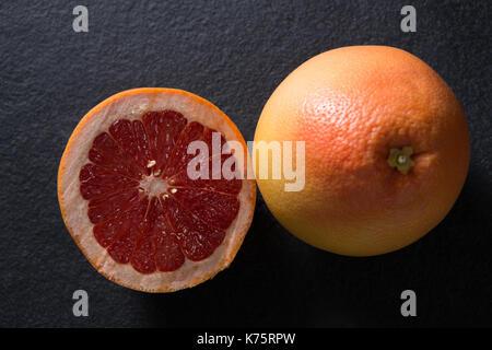 Close-up of grapefruit with half grapefruit on black background - Stock Photo
