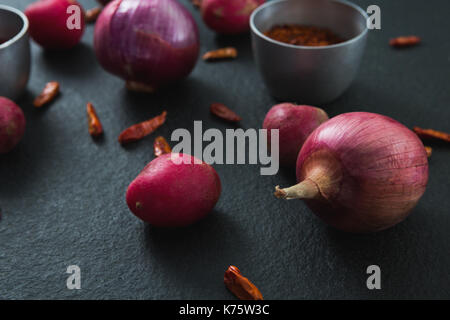 Close-up of onions and red pepper flakes on black background - Stock Photo