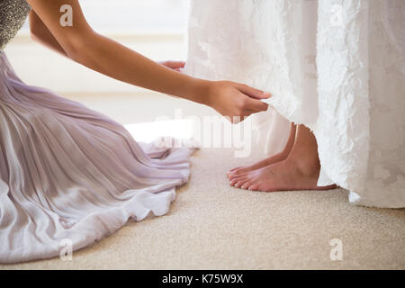 Midsection of bridesmaid assisting bride in getting ready at fitting room - Stock Photo