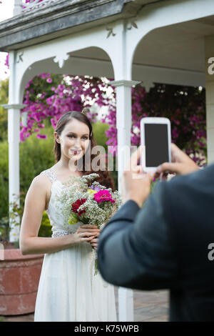 Cropped hands of bridegroom photographing bride holding bouquet at park - Stock Photo
