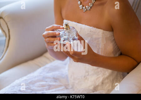 Midsection of bride holding perfume sprayer while sitting on armchair at home - Stock Photo