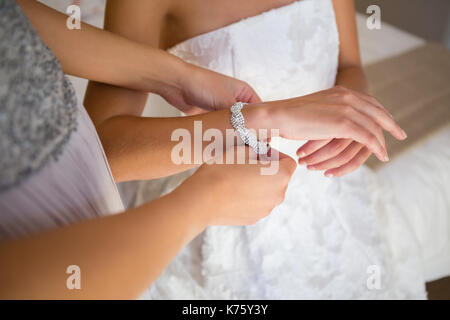High angle midsection of bridesmaid dressing bride in fitting room - Stock Photo